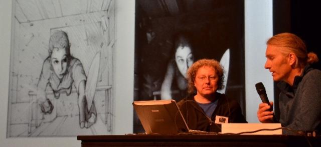 Die »Stellaris«-Kommandantin auf der Tischkante - Zeichner Conrad Schuebarg (i. e. Stefan Barton) erklärt Mitorganisator Gerhard Huber und dem Publikum, wie das Titelbild zur »Stellaris«-Kurzgeschichte 28 (»Absolute Finsternis« von Wim Wandemaaan) entstanden ist.
