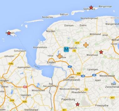 Der Mittelpunkt Osfrieslands ist mit einem M markiert. Die roten Sterne zeigen den westlichsten, nördlichsten, östlichsten und südlichsten Punkt an, die beiden gelben Kreuze den Mittelpunkt des Umquadrats (links) und den Schnittpunkt der Verbindungslinien. / Quelle: Google Maps
